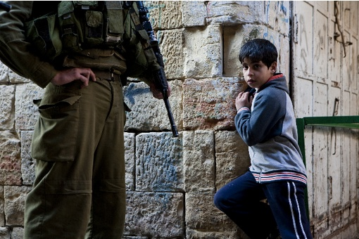 Israeli soldier and Palestinian boy in Hebron.